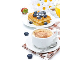 cup of cappuccino, belgian waffles with blueberries