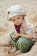 Kind sitzt nachdenklich im Sandkasten