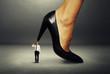 man with gun under big female heel