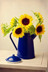 Sunflower bouquet in blue jug on wooden white table