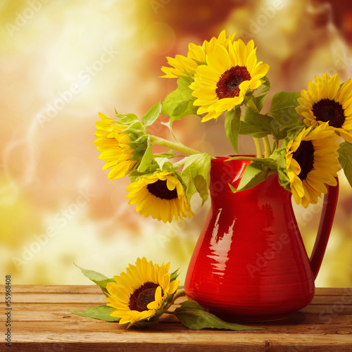 Sunflower bouquet in jug on wooden table over autumn bokeh