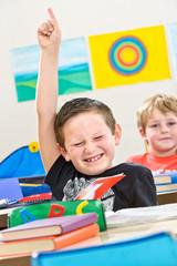 Junge zeigt auf im Klassenzimmer