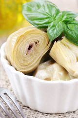 Artichoke hearts appetizer with a fresh leaf of basil
