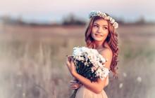 belle fille dans une gerbe de fleurs de camomille