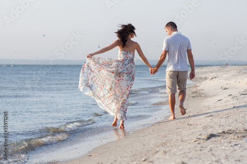Backview of walking couple among seashore during sunset