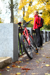 Girl cyclist with bike and backpack on bridge in autumn park