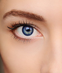 Macro bright blue eye of beautiful woman. Closeup portrait