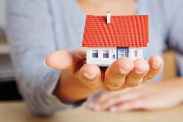 Frau hält kleines Haus auf der Hand