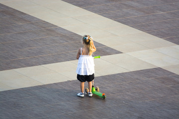 Little Girl Playing with Scooter