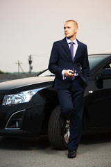 Young businessman with a cell phone at the car