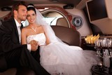 Bride and groom in limo smiling