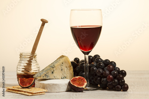 Still life with wine, cheese, honey and fruits