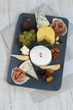 Appetizer with cheese, prosciutto and fruits