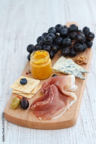 Rustic appetizer with cheese, prosciutto and grapes