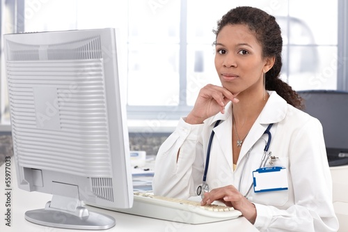 Portrait of young female doctor with computer