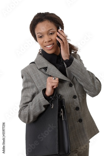 Ethnic businesswoman with mobile and bag