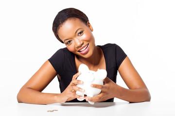 happy african woman holding piggybank