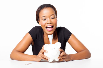 young african woman sitting with piggybank