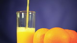 Three oranges and  juice which is pouring in  glass