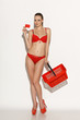 Woman in red bikini with empty shopping basket and credit card