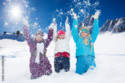 Three happy girls having fun with snow