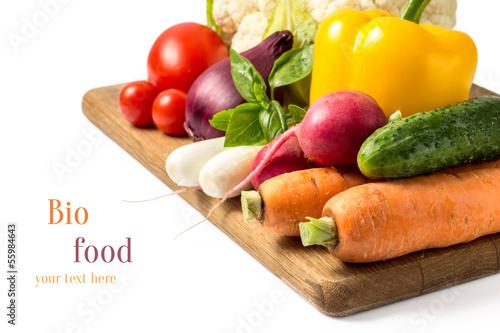 Fresh vegetables at wood cutting board isolated on white