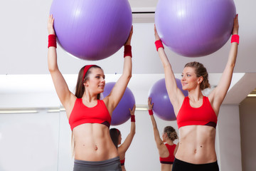 Two girls with fitballs in hands