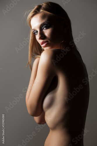 naked girl posing on gray background