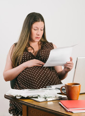 Pregnant Young Woman Paying Bills at Laptop Computer