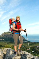 Mum walks with the child in the child carrying it.