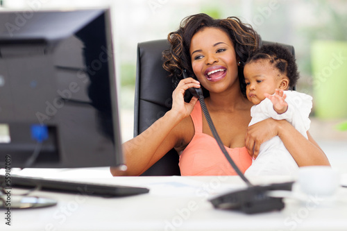 african businesswoman talking on landline phone while holding ba