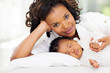 african woman lying in bed with her daughter