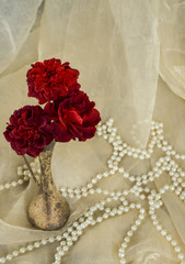 red roses in an antique silver vase
