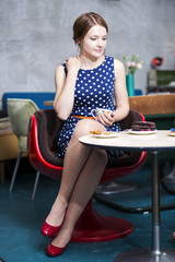Woman in white spotted dress hold cup