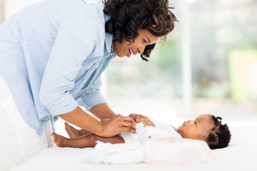 african american mother changing baby's diaper