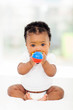 african baby girl biting her toy