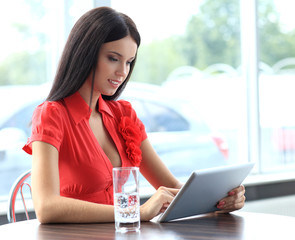 Happy young businesswoman using tablet computer in a office.