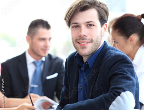 Happy businessman sitting in office