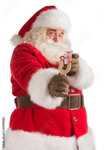 Portrait of happy Santa Claus aiming christmas gift with slingsh
