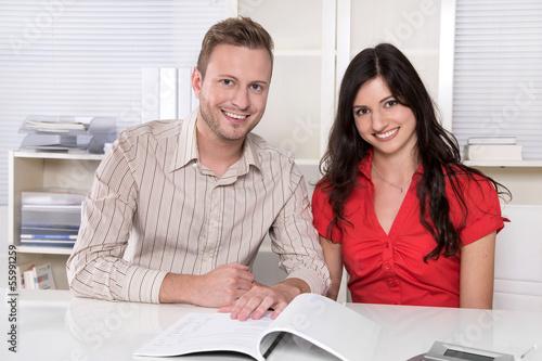 Junges Paar im Beratungsgespräch sitzend am Schreibtisch