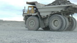 Heavy mining dump trucks moving along the opencast, closeup