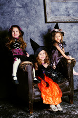 group of three little girl wearing in witch costumes celebrate H