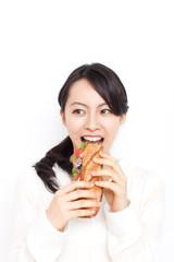 バゲットサンドを食べる女性