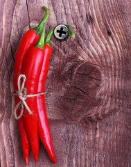 Red chilli pepper on wooden background.