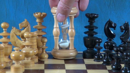 wooden chess pieces on chessboard and sandglass hourglass
