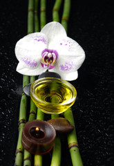 white orchid and bamboo grove ,candle,on wet