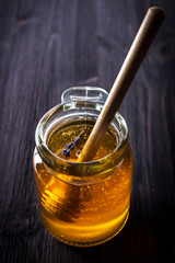 Pot of honey  with a wooden spoon