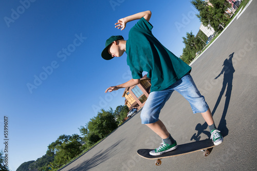 Cheerful boy riding a skateboard on the street.