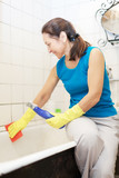 mature woman cleans bathtub with rug