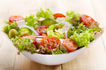 salad with vegetables and greens on wooden table